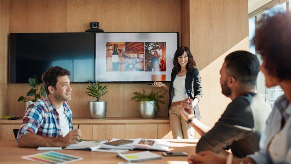 PowerPoint Endlosschleife: Frau steht vor einer Präsentation und lächelt