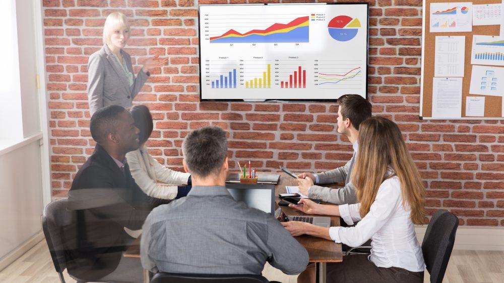 PowerPoint Wasserzeichen einfügen: Frau steht vor Präsentation und zeigt darauf