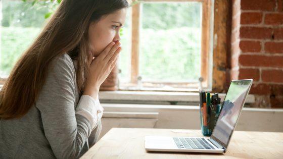 Junge Frau sieht erschrocken auf den Laptop-Bildschirm und überlegt, wie sie eine E-Mail zurückholen kann