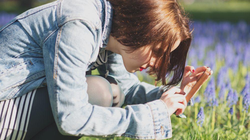 Junge Frau fotografiert Blumen mit dem Smartphone