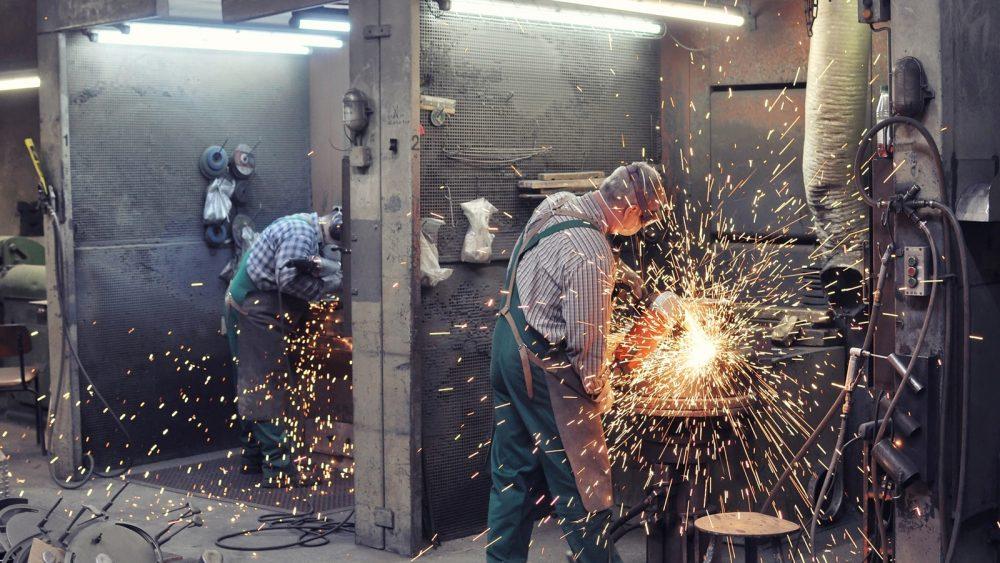 Industriefotografie: Männer arbeiten mit Metall und lassen Funken sprühen