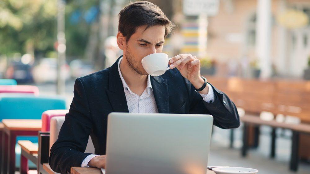 Mann sitzt kaffeetrinkend in einem Café und tippt mit angestrengtem Gesicht etwas in seinen Laptop.