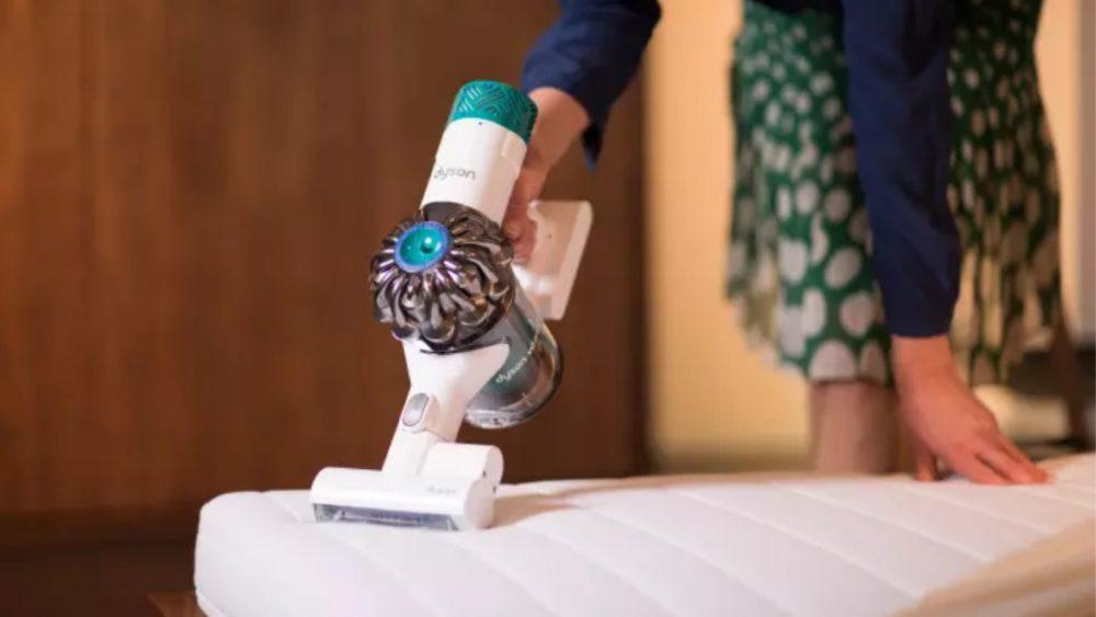 Frau saugt mit Dyson-Akkustaubsauger eine Matratze ab