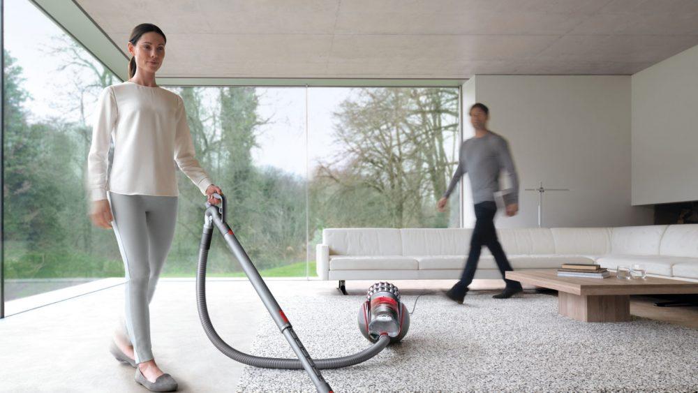 Pärchen saugt mit Dyson-Bodenstaubsauger durch eine helle Wohnung