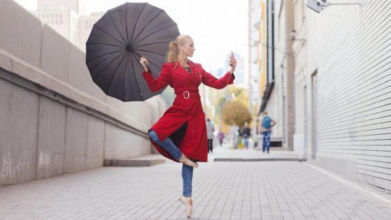 Junge Frau steht in Ballerina-Pose und mit Regenschirm auf der Straße und blickt auf Smartphone mit Regenradar-App