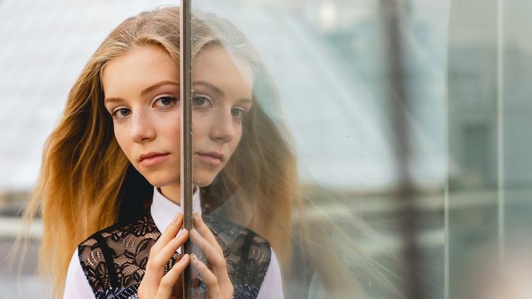 Spiegelung einer Frau in einer Glasoberfläche fotografiert