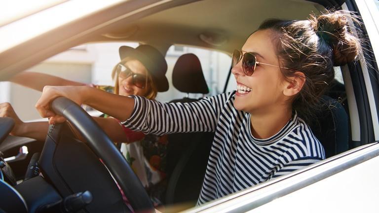 Zwei Freundinnen fahren Auto und haben Spaß