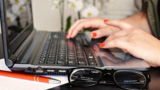 Notebook mit Hand auf Tastatur, im Vordergrund Kuli und Brille