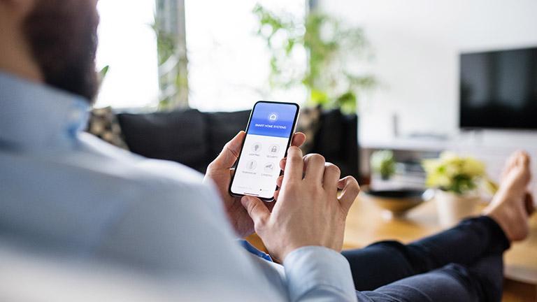 Person mit Smartphone steuert smarte Beleuchtung