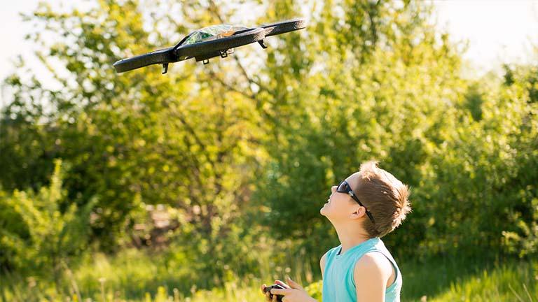 Kind steuert draußen in der Natur eine Drohne