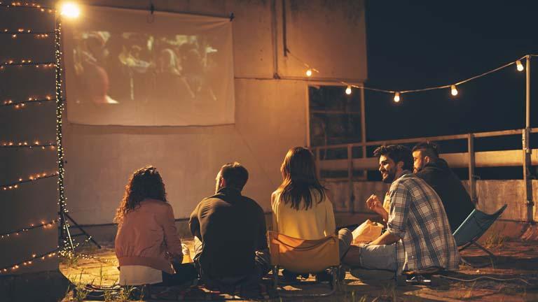 Eine Gruppe junger Leute nutzt Heimkino im Freien