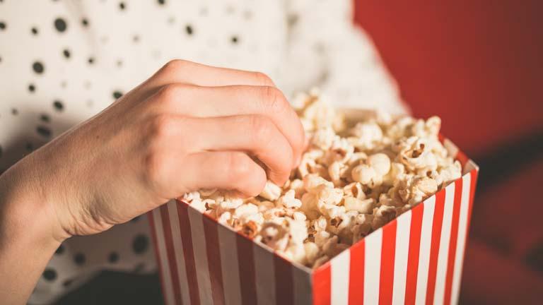 Frau isst Popcorn im Heimkino