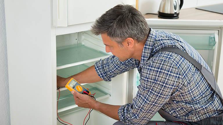 Ein Techniker testet den Thermostat eines Kühlschranks im Gerät