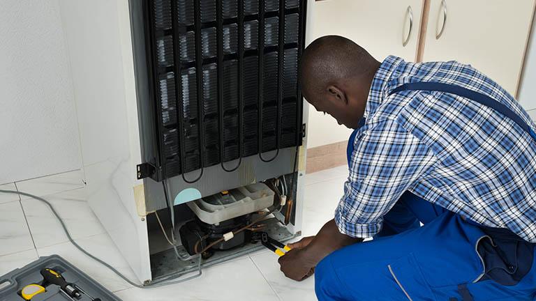 Ein Techniker arbeitet mit einer Zange am Kompressor eines Kühlschranks