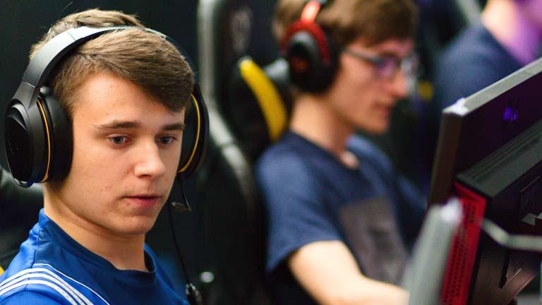 Zwei junge Männer spielen an zwei PS4 und tragen dabei ein Headset