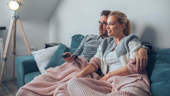 Paar sitzt auf der Couch und schaut Fernsehen übers Internet