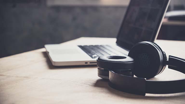Laptop und Bluetooth-Kopfhörer auf Holztisch