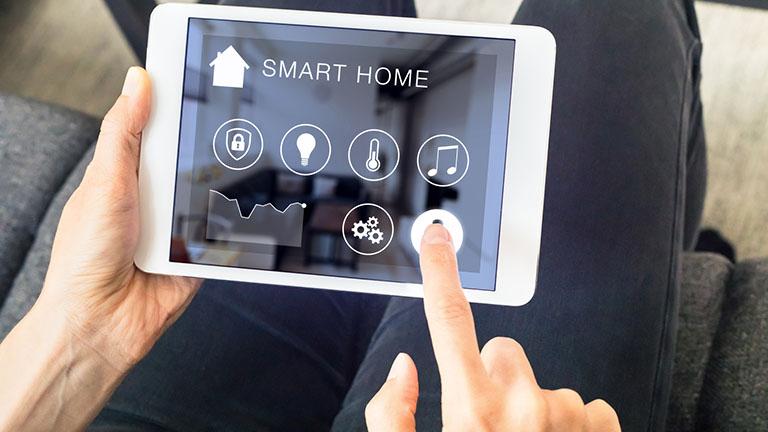 Frau stellt auf Tablet Smart-Home-Features ein