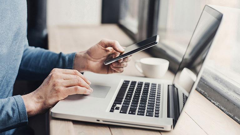 Mann arbeitet unterwegs am MacBook