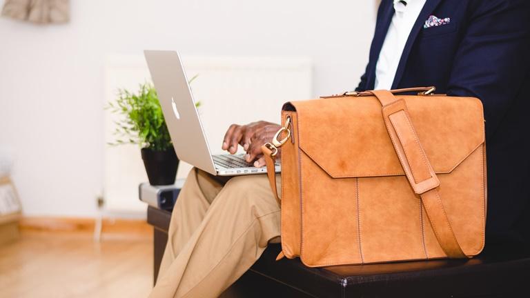 Mann hat MacBook auf dem Schoß