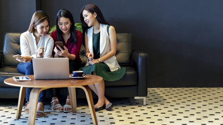 Freundinnen sitzen im Cafe und schauen auf Smartphone und Laptop