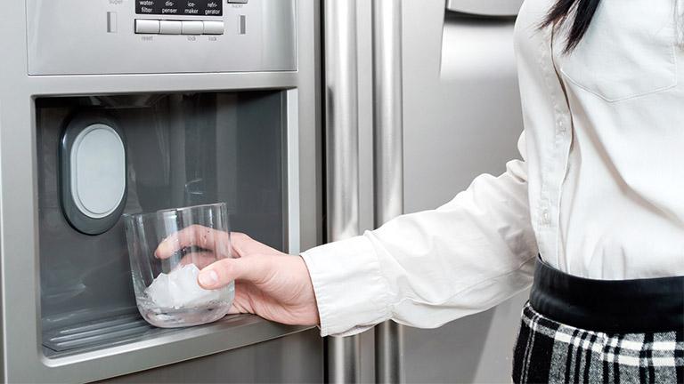 Eine Frau nutzt den Side-by-Side-Kühlschrank, um sich im Sommer mit Eiswürfeln abzukühlen