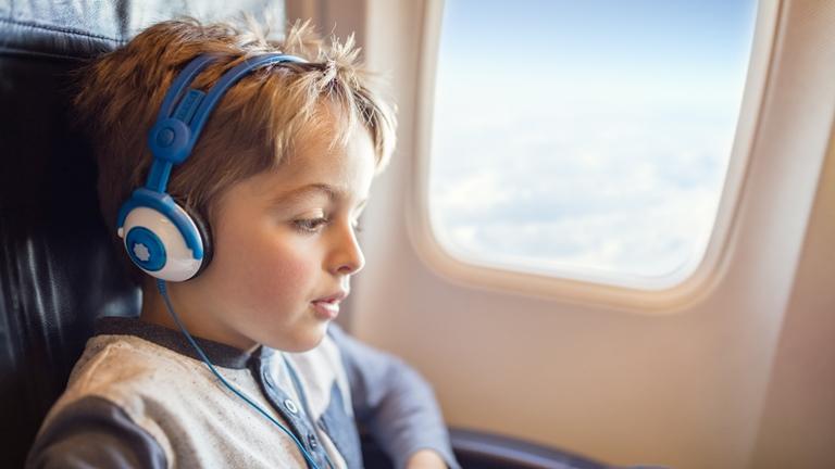 Junge hört Toniebox im Flugzeug