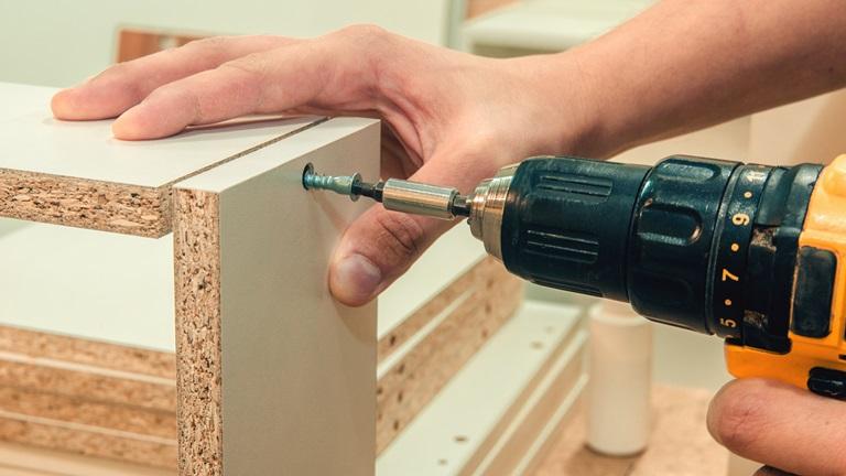 Heimwerker schraubt zwei Holzplatten aneinander