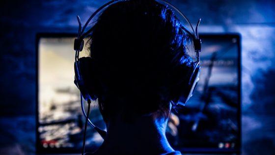 Eine Frau mit Kopfhörern nimmt ein Let's Play als Screencast auf