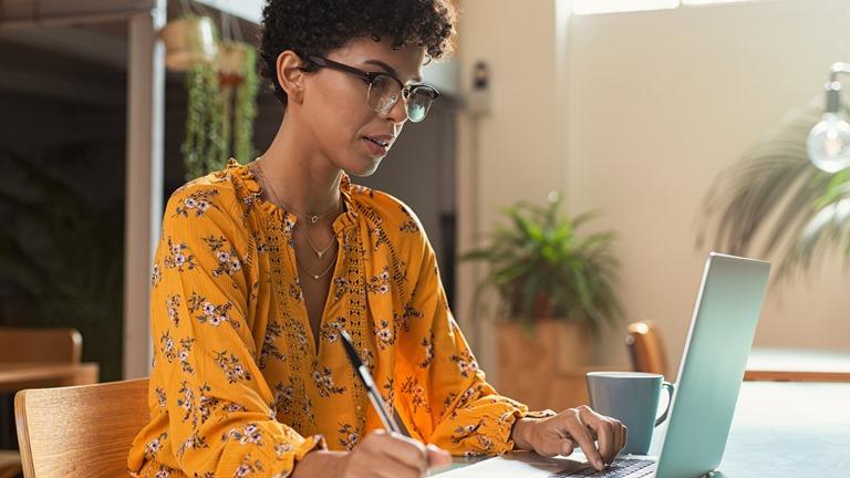 Eine Frau mit Laptop macht sich Notizen für einen Screencast