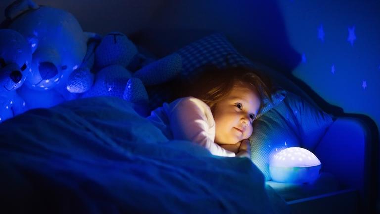 Kleines Mädchen liegt im Bett mit Sternenhimmel-Projektor