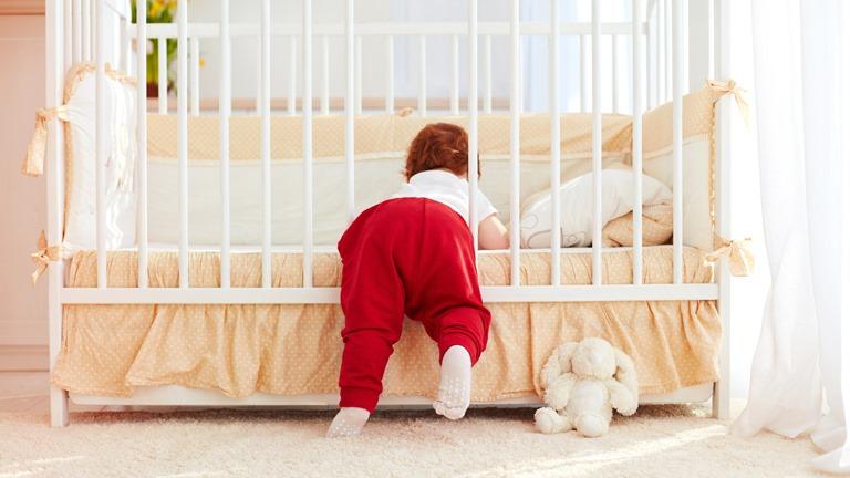 Kleines Kind klettert aus dem Gitterbett