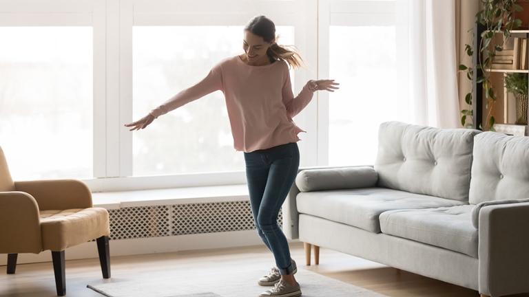 Eine Frau tanzt zu Musik aus ihrem Sonos-Lautsprecher im Wohnzimmer