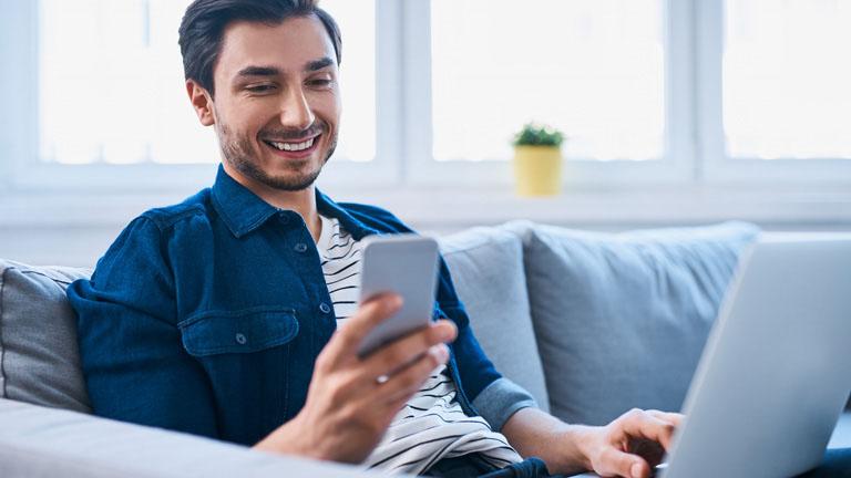 Mann mit Notebook auf den Schoß ruft seinen Internetanbieter mit dem Handy an