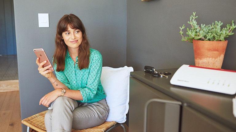 Frau verbindet ihr Smartphone per WLAN mit der FritzBox