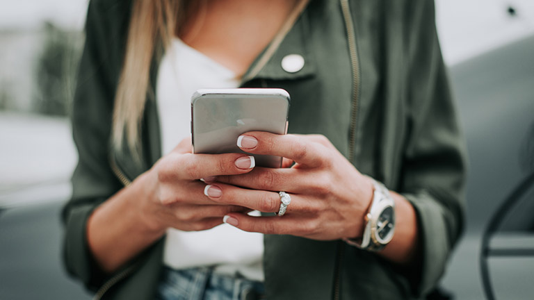 Frau blickt aufs Handy und ärgert sich