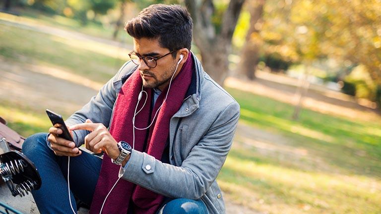 Mann am Smartphone spricht über seine Kopfhörer