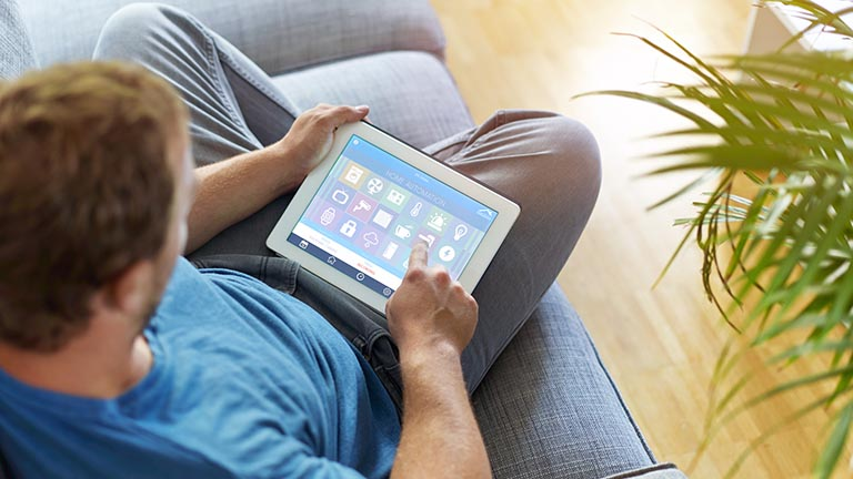 Smart-Home-Hub: Mann verwendet Smart-Home-Zentrale, um das intelligente Zuhause zu steuern