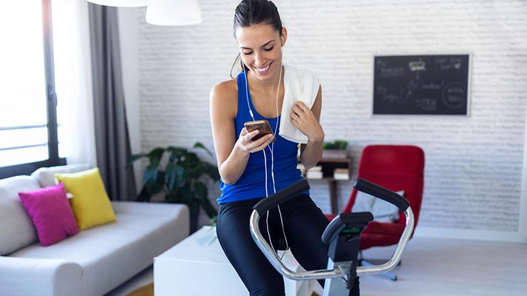 Frau trainiert zu Hause auf Fitnessgerät
