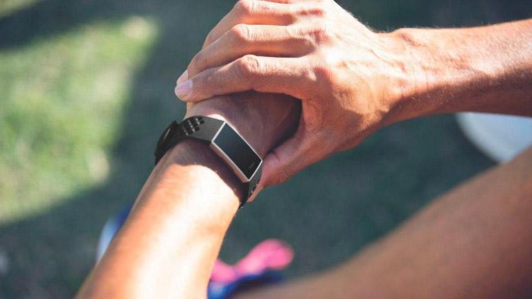 Person mit Fitnesstracker am Handgelenk