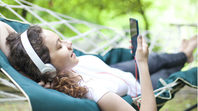 Frau liegt in einer Hängematte im Garten und surft übers Smartphone im Internet