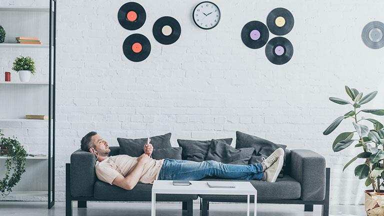 Mann auf Couch hält Smartphone