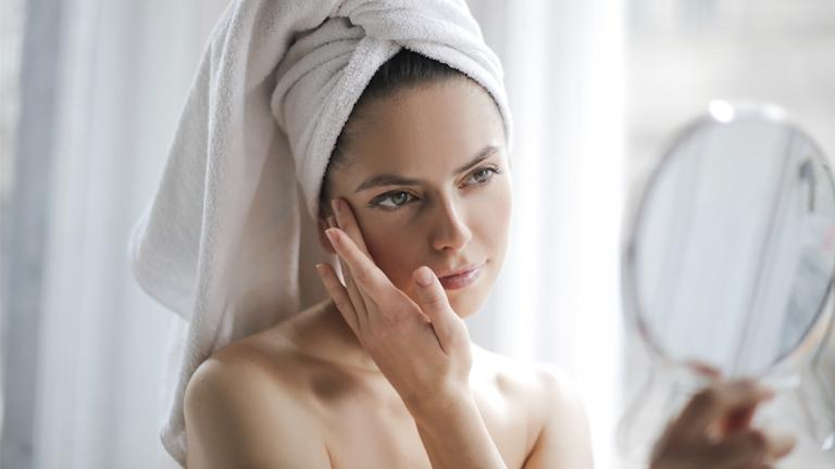 Frau schaut sich Gesichtshaut im Spiegel an