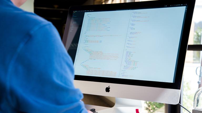 Mac mit Code auf Bildschirm