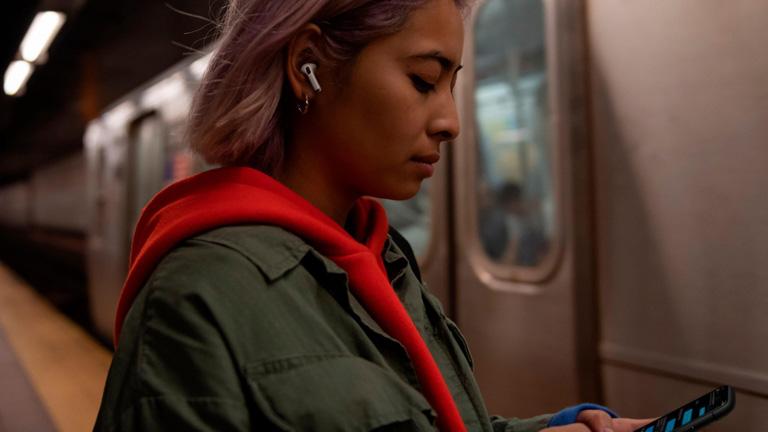 Frau mit AirPods und Smartphone