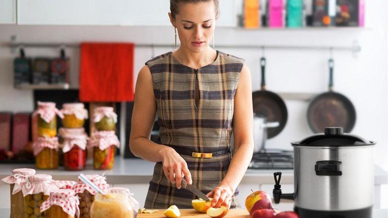 Frau schneidet Äpfel für den Einkochautomaten