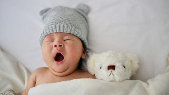 Gähnendes Baby mit Strickmütze und Teddy im Bett