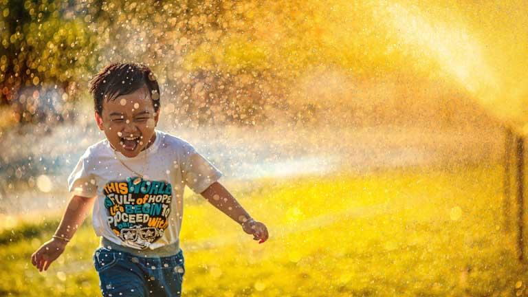 Junge läuft lachend durch Sommerregen