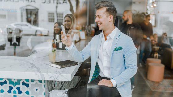 Mann mit Smartphone an Bar