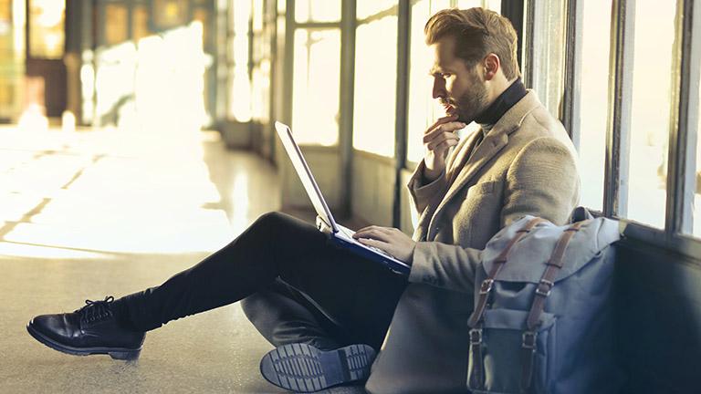 Mann mit Laptop am Flughafen